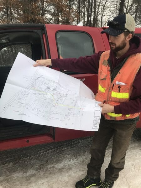 Pine Ridge Land Surveying employee Kurt Tibbals with the survey plans